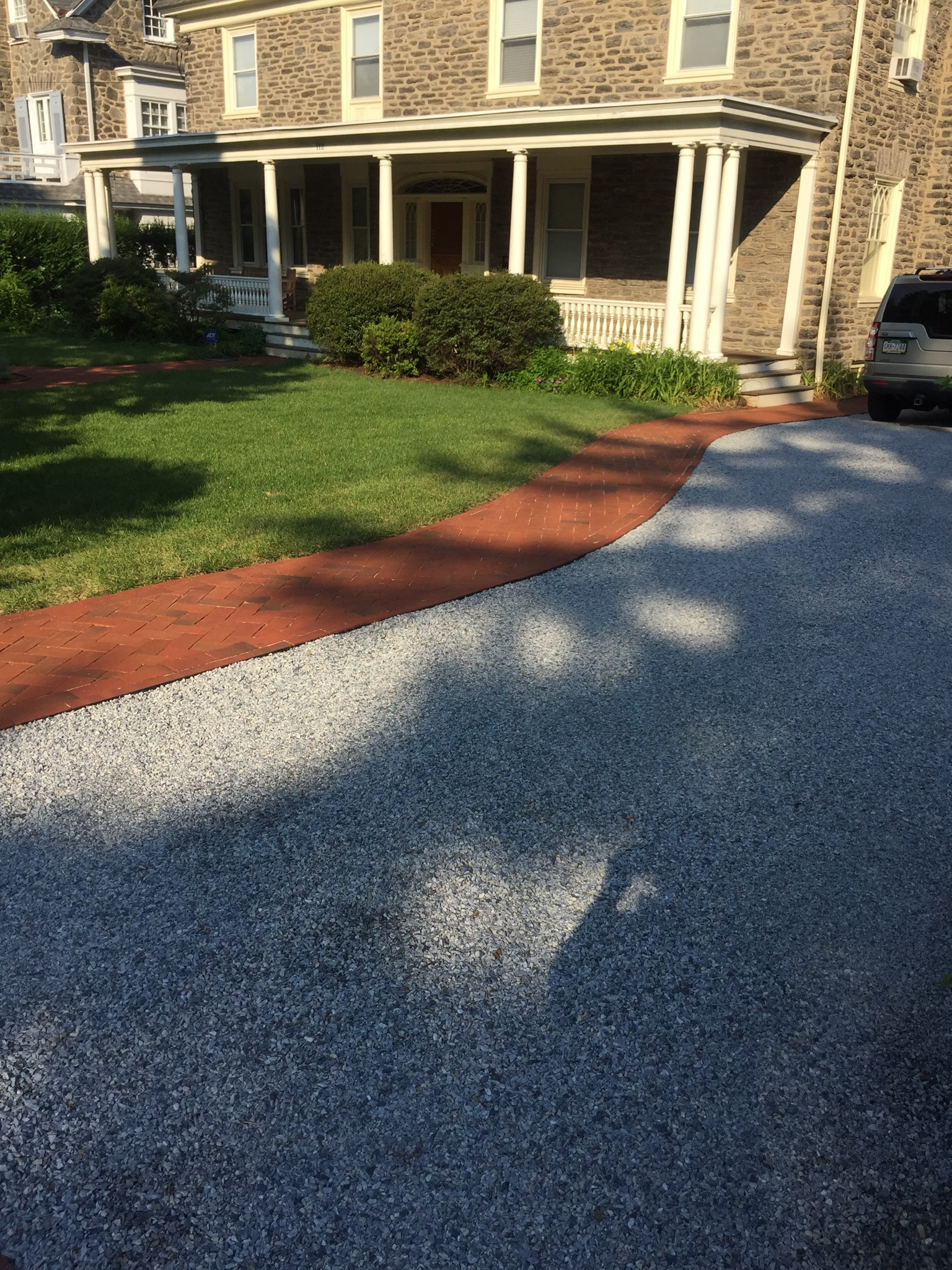 Crushed stone driveway with brick walkway